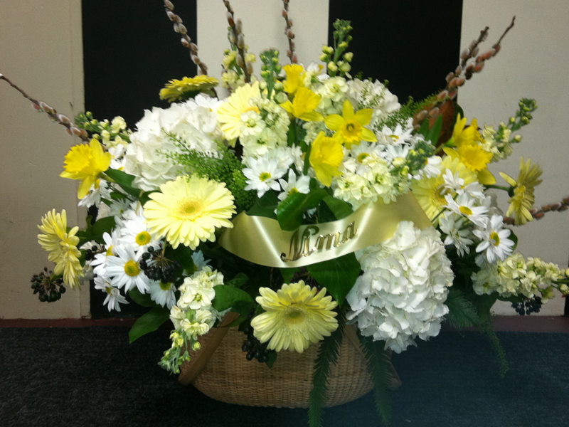 Yellow and white funeral flower arrangement